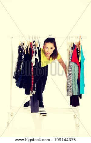 Young beautiful woman with clothes on hanger.