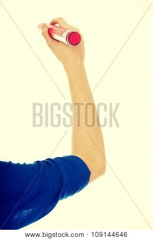 Woman's hand writing with oversized pencil.