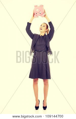 Happy business woman shaking a piggybank.
