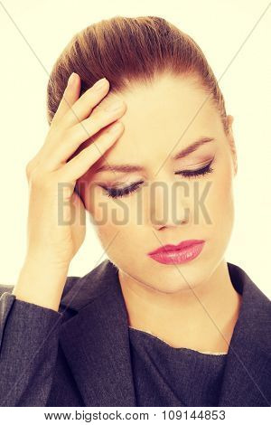 Young businesswoman suffering from headache.