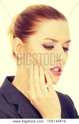 Young businesswoman suffering from tooth ache.