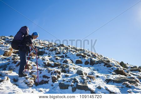 Mountaineer Climbing A Snowy Slope.