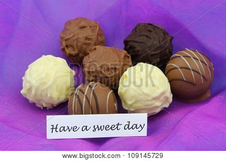 Have a sweet day card with assorted chocolates, truffles and pralines on purple background
