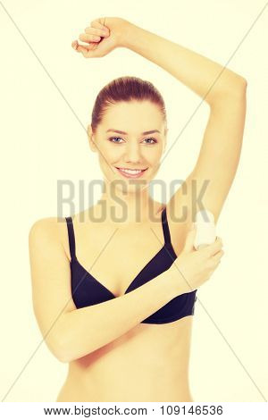 Woman in underwear applying antiperspirant.
