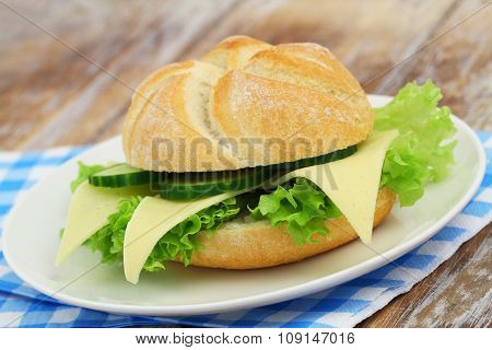 Freshly baked bread roll with cheese, lettuce and cucumber