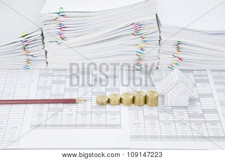 Step Pile Of Gold Coins Between Brown Pencil And House