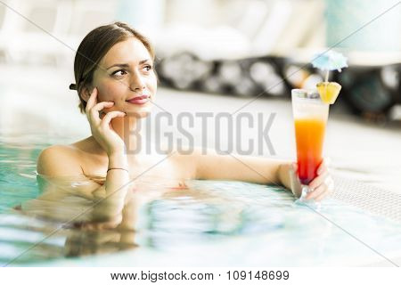 Beautiful Young Woman Drinking A Cocktail While In The Swimming Pool
