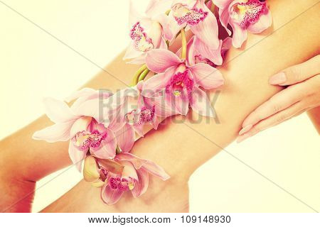 Slim long woman legs with pink flowers.