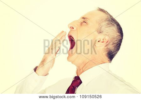 Exhausted and sleepy businessman yawning.