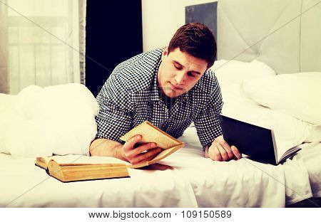 Handsome thoughtful man with a book in his bed.