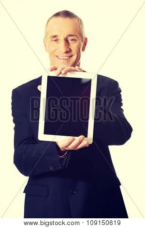 Smiling mature businessman holding digital tablet.