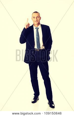 Full length businessman pointing upwards.
