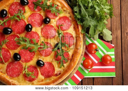 Tasty pizza with salami on decorated wooden table, close up