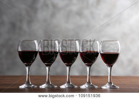 Half full wine glasses on table on light background