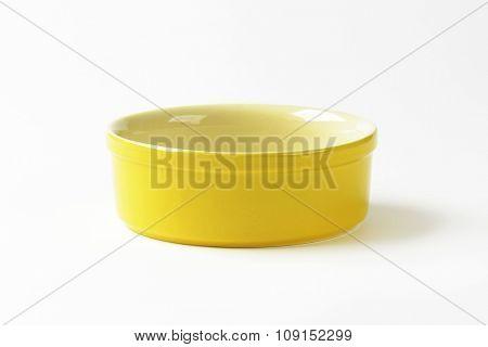 Small empty yellow souffle dish