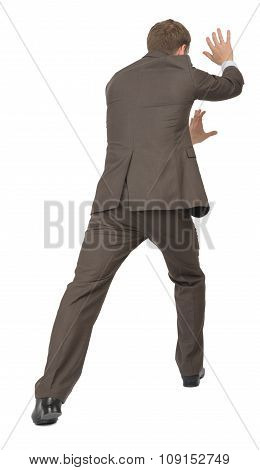 Businessman pushing empty space, rear view