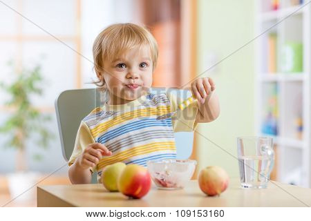 child eating healthy food with a spoon at home