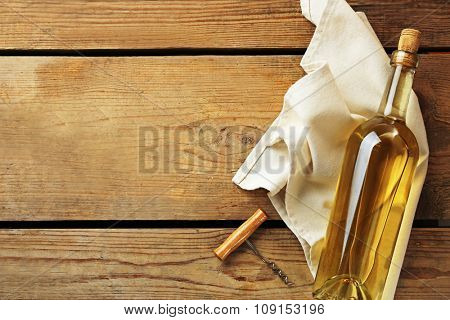Bottle of wine with a corkscrew on wooden background