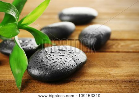 Spa stones and bamboo branch on wooden background