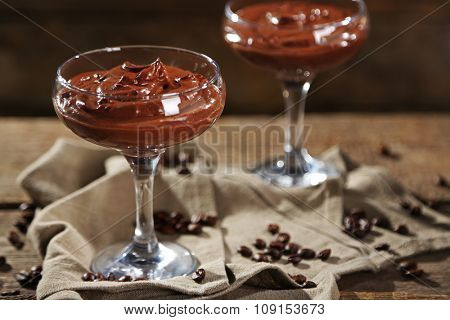 Chocolate dessert in glasses on wooden background