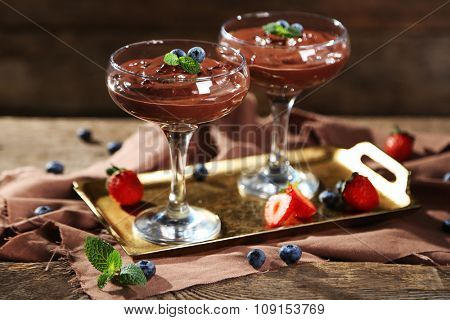 Chocolate dessert in glasses and fresh berries on color wooden background