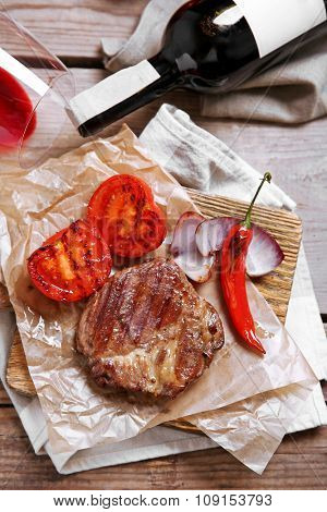 Roasted beef fillet and vegetables on cutting board, on wooden background