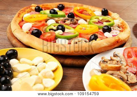 Delicious pizza and ingredients at the restaurant, close-up