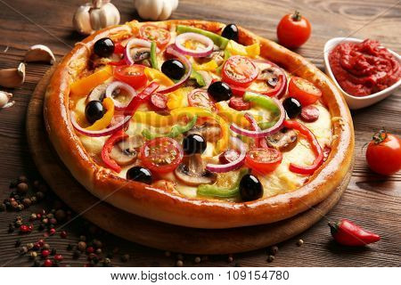Delicious pizza with vegetables, on wooden table, close-up