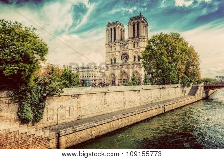Notre Dame Cathedral in Paris, France and the Seine river embankment on a sunny day. Vintage