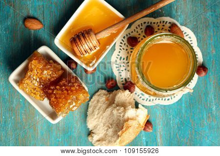 Honeycomb, glass pot with honey and nuts on color wooden background