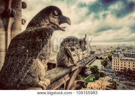 Gargoyles and chimera statues of Notre Dame over Paris, France skyline. Dark clouds, vintage