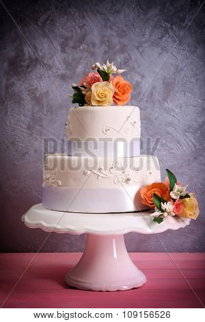 White wedding cake decorated with flowers on  pink wooden table against grey background