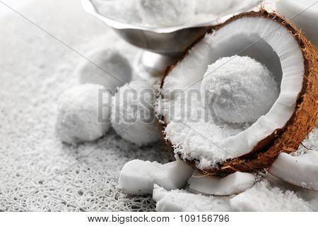 Homemade Candies in coconut flakes and fresh coconut on light background