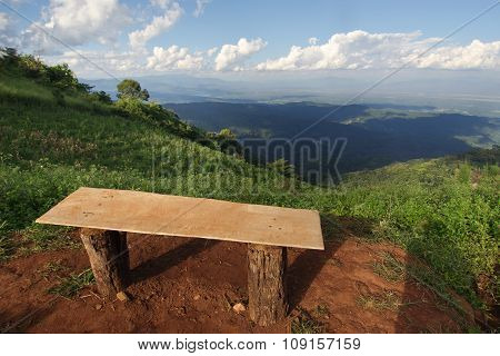 Lonely chair with grass, mountain and cloudy sky view of Chiangmai Thailand
