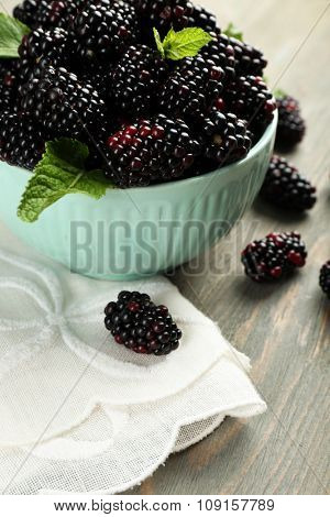 Heap of sweet blackberries with mint in bowl on table close up