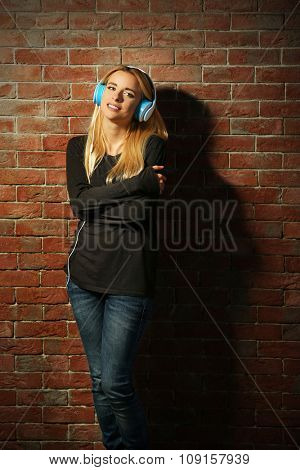 Young woman standing at the brick wall and listening to music