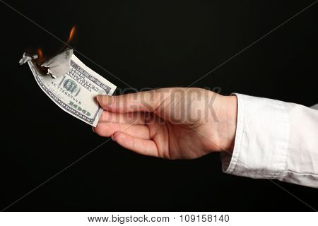Woman burning dollars on black background