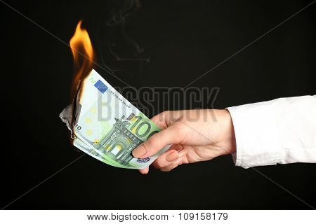 Woman burning Euros banknotes on black background