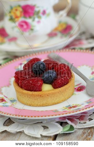 Delicious crunchy tartelette with custard, fresh raspberries and blueberries with cup of tea