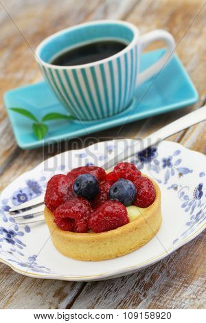 Crunchy tartelette with fresh fruit and cup of coffee on rustic wooden surface