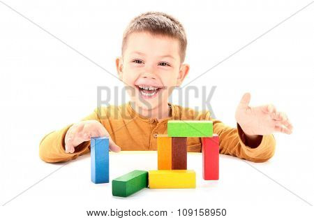 Happy boy is playing with wooden blocks toy