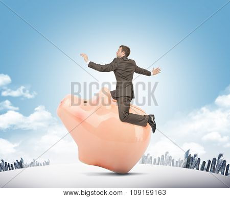 Businessman sitting on pink piggy bank