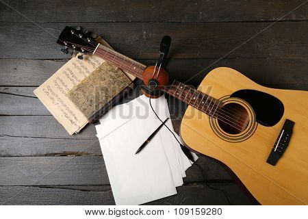 Acoustic guitar, headphones, musical notes and white papers on wooden background