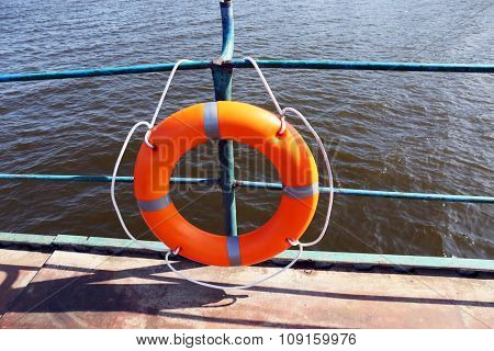 A life buoy hangs on the pier's handrail