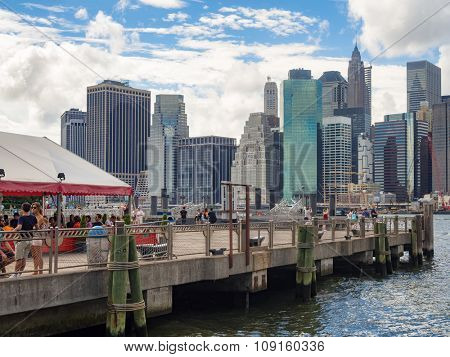 NEW YORK,USA - AUGUST 20,2015 : People at a pier in Brooklyn with the Lower Manhattan skyline on the background