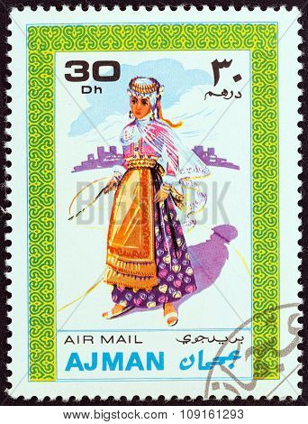AJMAN EMIRATE - CIRCA 1968: Stamp shows a woman in traditional costume