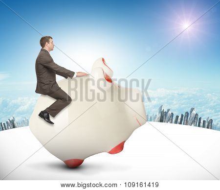 Man sitting on white piggy bank, side view