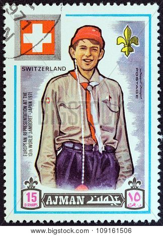 AJMAN EMIRATE - CIRCA 1971: A stamp printed in United Arab Emirates shows boy scout from Switzerland