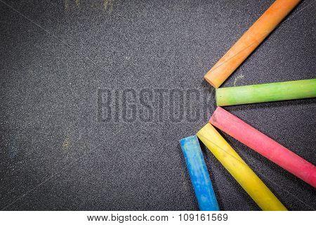Row of rainbow colored chalk on blackboard