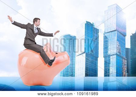Man sitting on white piggy bank and city